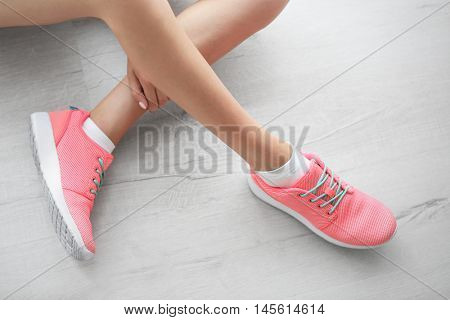Woman wearing pink sneakers on wooden floor background