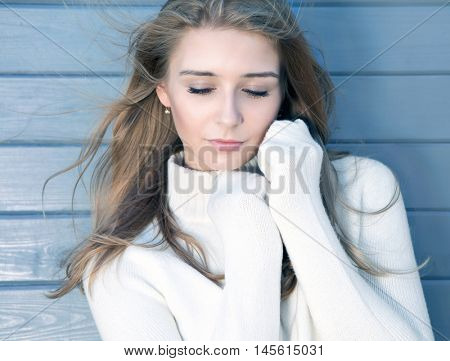 Beautiful natural young  blonde woman with eyes closed wearing knitted sweater. Cold fall and winter fashion beauty concept