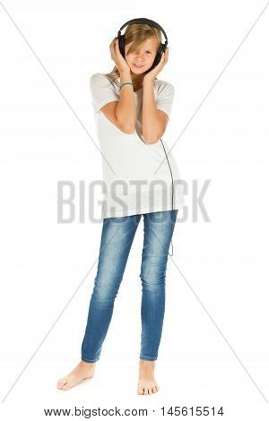 Young girl standing listening to music with headphones over white background