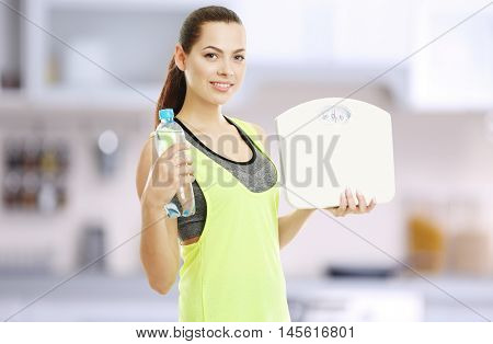 Young beautiful woman with bottle and scales on blurred kitchen interior background.