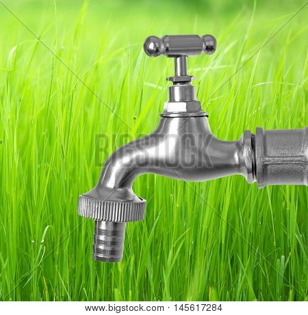 Conservation water concept. Metal faucet on green grass background.