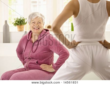 Senior woman doing exercises demonstrated by personal trainer, looking at camera, smiling.?