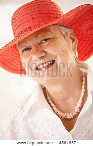 Closeup portrait of happy senior woman wearing hat, looking at camera, smiling.?