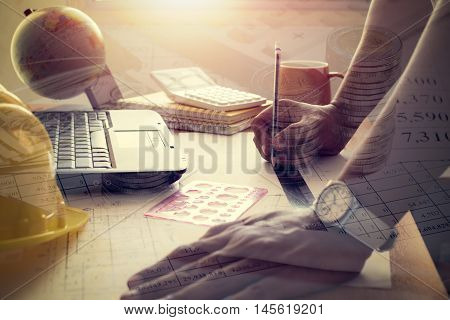 Hands of architect drawing construction plan. Double exposure photo finance accounting and investment under shinning light
