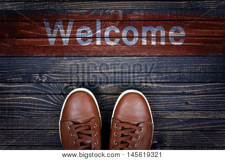 Welcome message and sport shoes on wooden floor