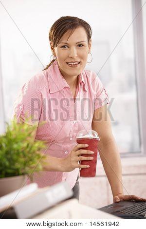 Empresária de pé no balcão, segurando a xícara de café, olhando para a câmera, sorrindo.?