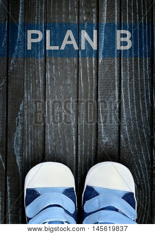 Plan B message and kid shoes on wooden floor