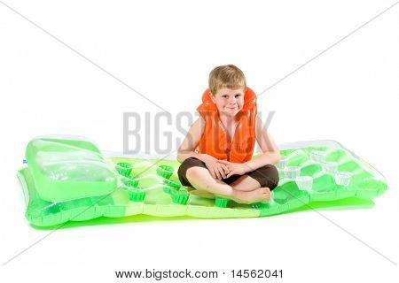 Little boy sitting on green inflatable mattress, wearing orange life vest. Isolated on white.?