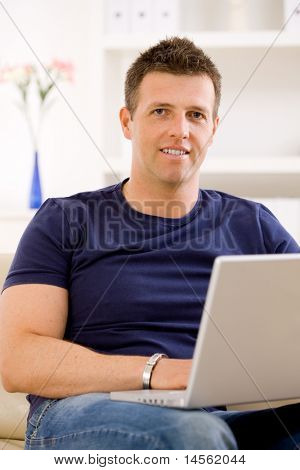 Man sitting on sofa at home and using laptop computer.?