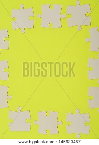 White puzzle pieces isolated on a yellow background