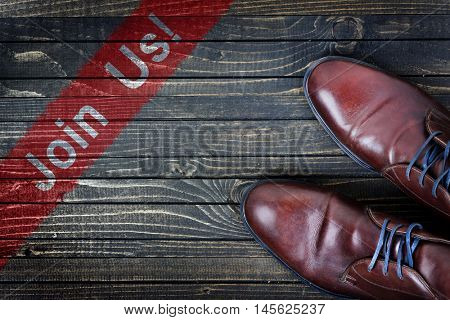 Join Us message and business shoes on wooden floor