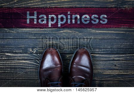 Happiness message and business shoes on wooden floor