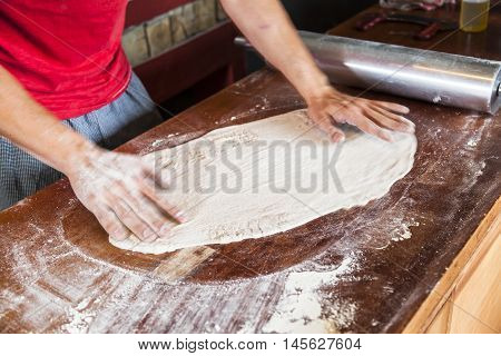 Chef preparing pizza spreading the mass on wood table