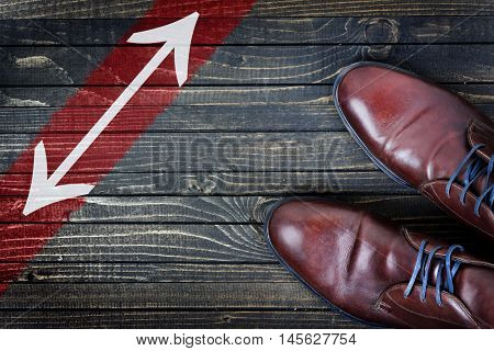 Arrows message and business shoes on wooden floor