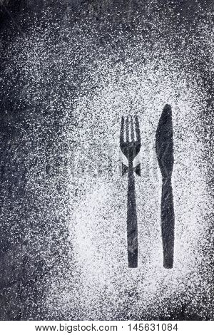 Knife and fork imprint in powdered sugar on a stone table.