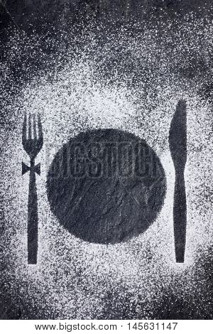 Knife fork and plate imprint in powdered sugar on a stone table. Copy space for your text.