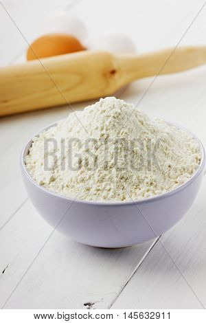 Flour in ceramic bowl with eggs and rolling pin on a white wooden background. Bakery concept.
