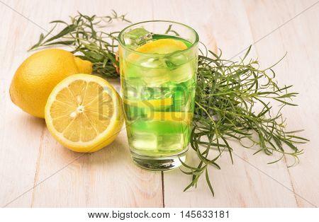 Glass of fresh homemade lemonade with tarragon and lemon on wooden table