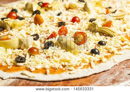 Chef preparing vegetarian pizza applying vegetables and chees