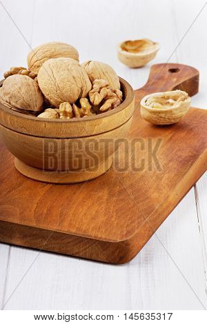 Walnuts in a wooden bowl on a brown board.