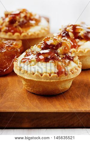 Tartlets with ricotta cheese decorated nuts, apple and caramel. Great homemade dessert.