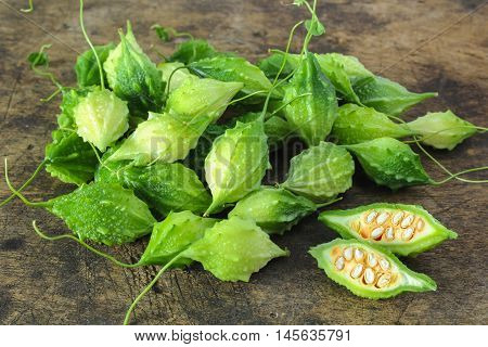 green bitter gourds on wooden background, vegetable