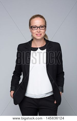 Beautiful young caucasian woman in business attire wearin black eyeglasses. Style portrait on grey background.