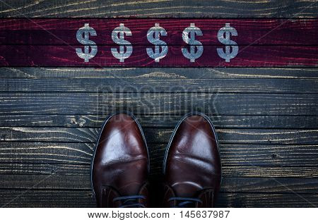 Dollar sign message and business shoes on wooden floor