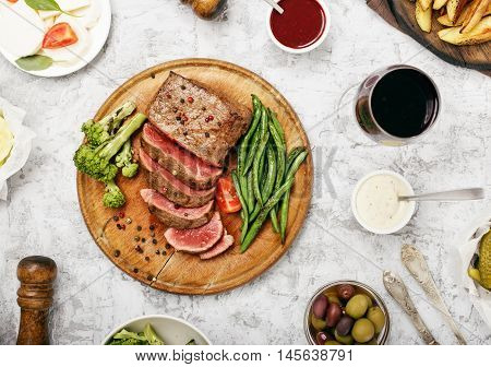 Steak with side dish of French beans and glass of red wine on a wooden board top view