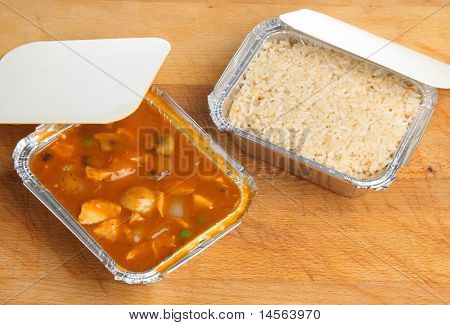 Chinese chicken curry with egg fried rice in foil takeaway containers.