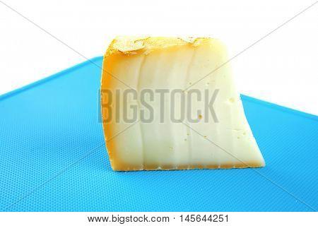 light swiss gauda cheese on blue board