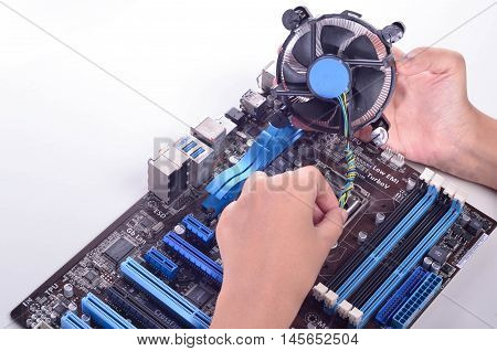 computer motherboard isolated in whitebackground with a person hand placing a fan cooler into the motherboard