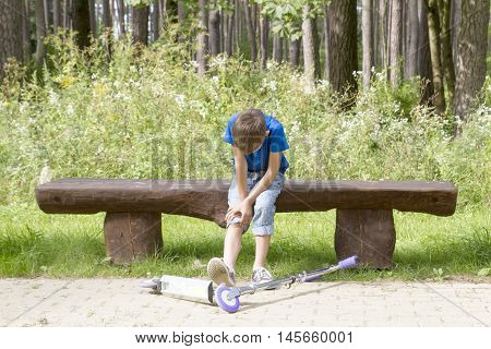 Boy sitting on the wooden bench in the park. Child felt while riding his scooter and hurt his leg.