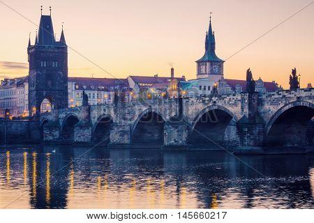 Prague city sunrise over Charles Bridge on Vltava river. Czech Republic