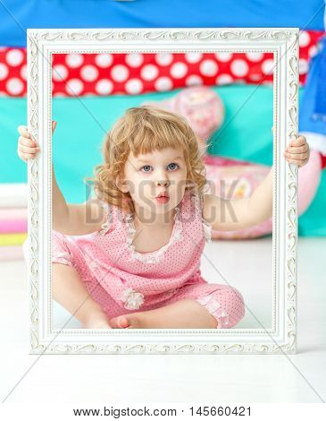 Little cute girl in a pink suit sitting on the floor and play the ape over a wooden white frame.