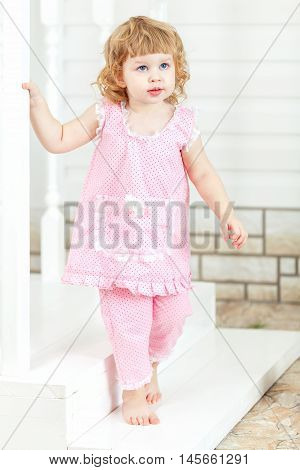 Little curly girl in a pink dress and bare feet coming out of the house and go down the stairs.
