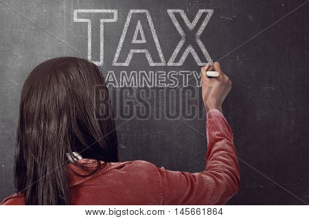 Business woman writing tax amnesty quotes on the black board with chalk