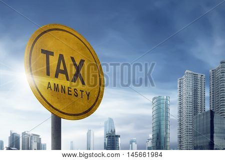 Tax amnesty quotes on the board traffic signs on the outdoor with blue sky and skyscraper background