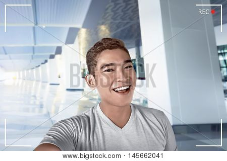 Young asian man pose selfie in airport lobby alone smile expression and cheerful