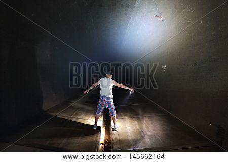 Man in a dark horror underground tunnel.