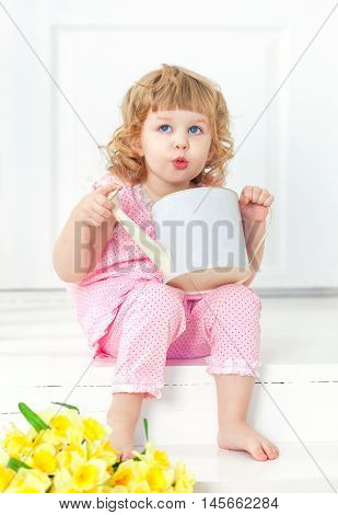 Little curly girl in a pink dress and barefoot sits on a white porch and playing with children's watering can.