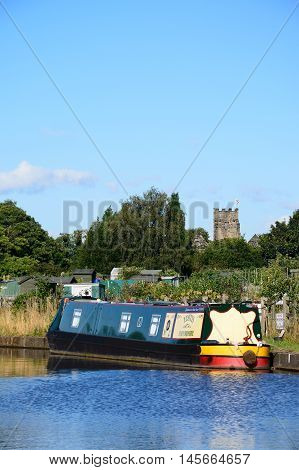 ARMITAGE, UNITED KINGDOM - AUGUST 8, 2016 - Narrowboat moored on the canal with allotments and church to the rear Armitage Staffordshire England UK Western Europe, August 8, 2016.