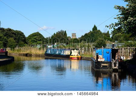 ARMITAGE, UNITED KINGDOM - AUGUST 8, 2016 - Narrowboats moored on the canal with allotments and church to the rear Armitage Staffordshire England UK Western Europe, August 8, 2016.