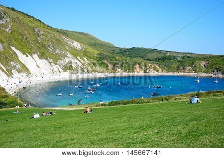 LULWORTH COVE, UNITED KINGDOM - JULY 19, 2016 - View looking down the hillside towards the cove with tourists sitting on the grass in the foreground Lulworth Cove Dorset England UK Western Europe, July 19, 2016.