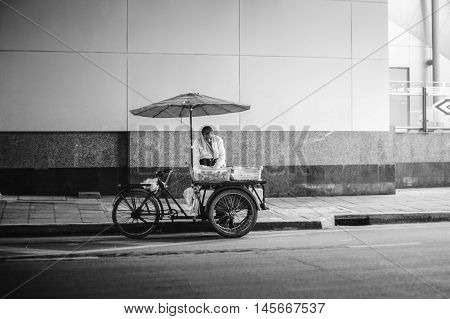 Bangkok Thailand -July 17 2016: old man vender wait for a customer on a street in bangkok province thailand black and white color picture style selective focus
