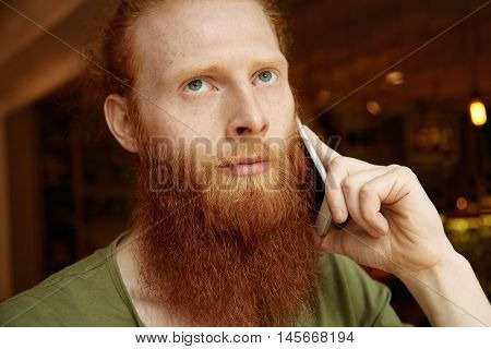 Young Redhead Student Making Phone Calls With Concentrated Expression, Listening Attentively, Lookin