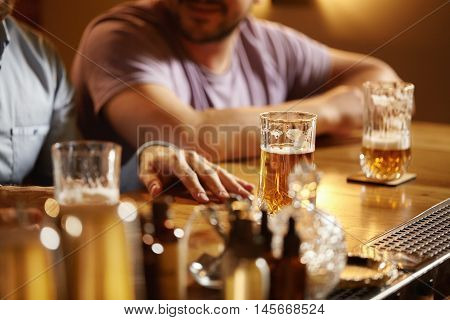 People, Leisure And Friendship. Old Friends Meeting, Talking, Drinking Light Beer At Pub. Young Men