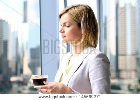 Portrait of business woman standing with coffee near window. Downtown area background