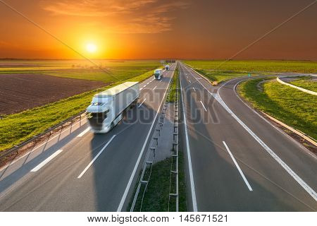 Three new white trucks driving towards the sun. Fast blurred motion drive on the freeway at beautiful sunset. Freight scene on the motorway near Belgrade Serbia.