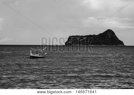 Traditional Fishing Boat Laying Alone On The Sea With Island In Background ,selective Focus,black An